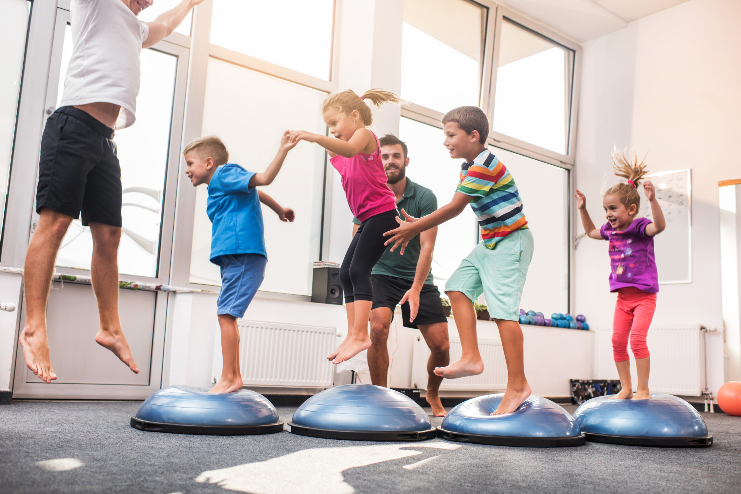 Happy children having fun while jumping on bosu balls on sports training in a health club. Male coaches are with them.